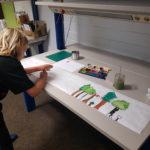 Ein Kind bemalt eine lange Papierbahn