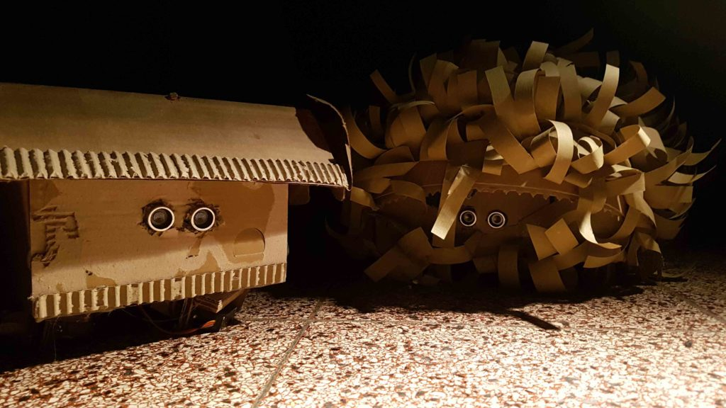 """Zwei kleine Maschinenwesen aus Pappe aus der Installation """"Ein Platz an der Sonne"""""""