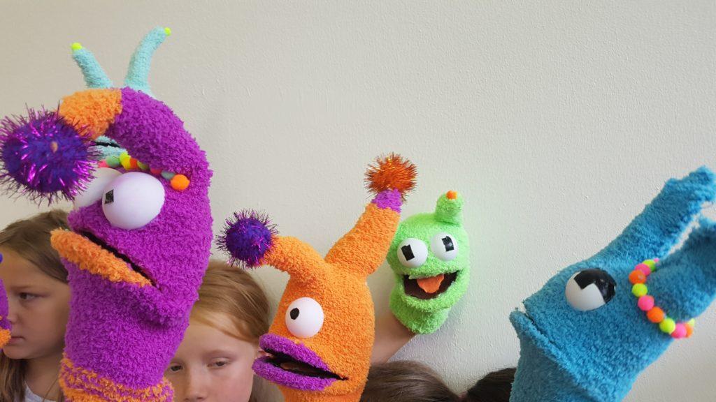 Kinder mit selbst gebauten Sockenpuppen in einem Theaterpädagogikprojekt