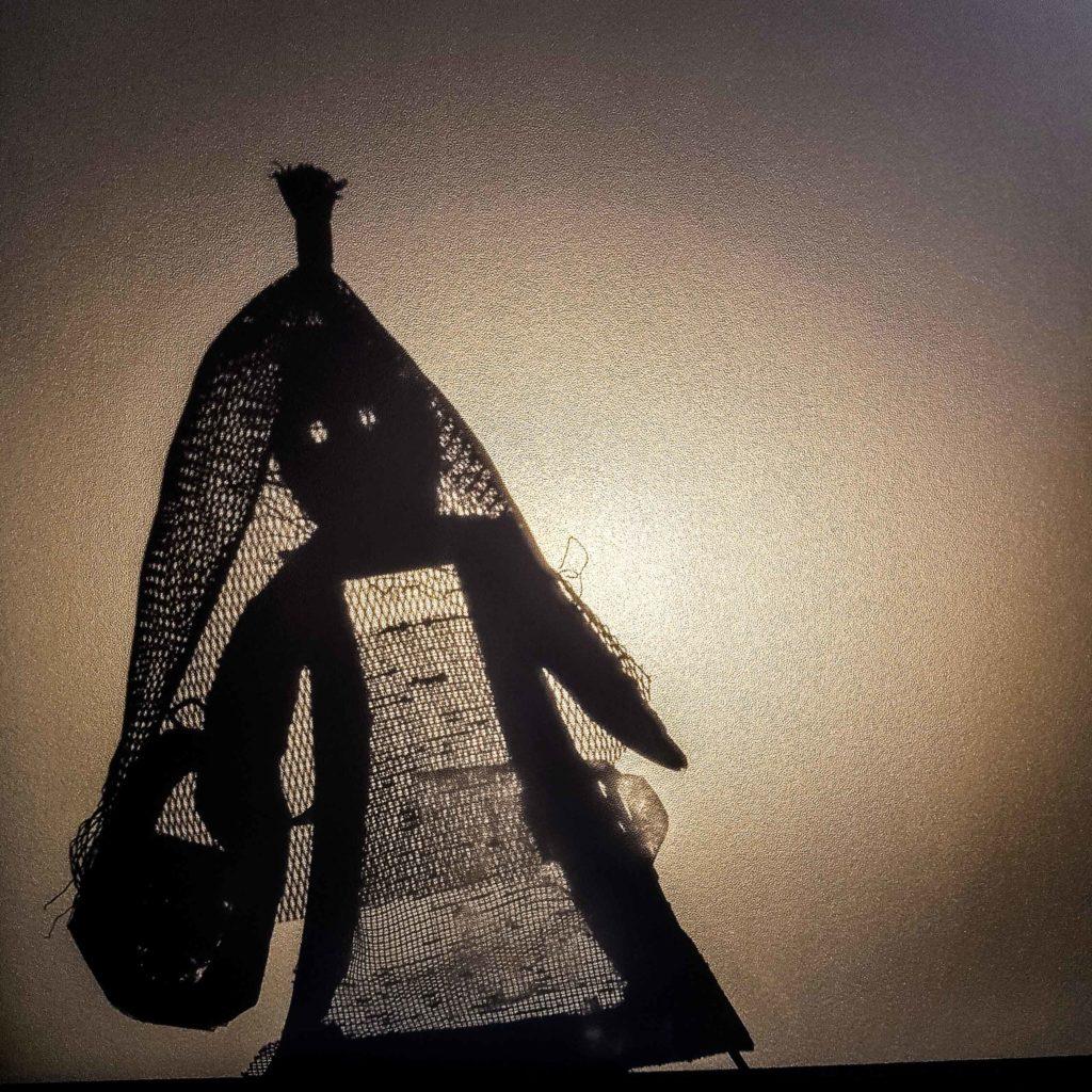 Eine kleine Schattentheaterfigur hergestellt aus Pappe und einem Knoblauchnetz.