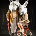 Das Bild zeigt zwei Maskenspieler. beide tragen Eselmasken und sind als altes Ehepaar gekleidet.