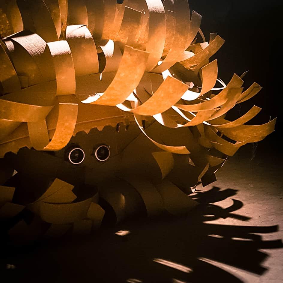 """Das Bild zeigt einen Roboter mit wilden Papierlocken aus der Installation """"Ein Platz an der Sonne""""."""