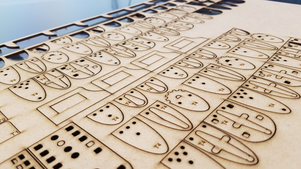 """Das Bild zeigt frisch gelaserte Bauteile aus MDF, die zur Herstellung der Roboter aus der Installation """"Ein Platz an der Sonne"""" benutzt werden."""