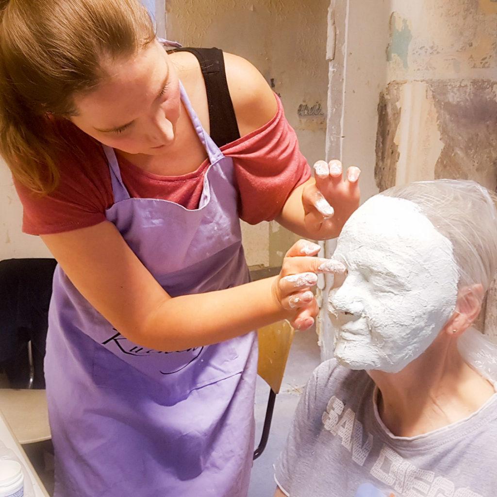 Eine Frau gipst das Gesicht einer anderen ab.
