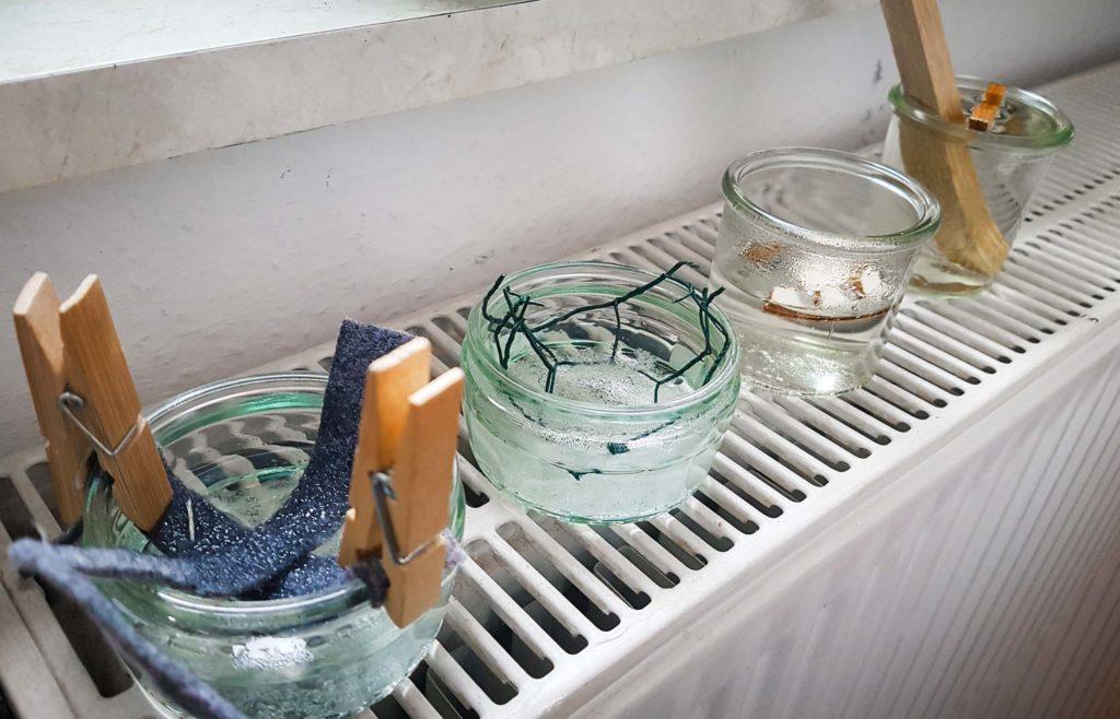 Kristalle aus Alaunsalz wachsen in vier Glasbehältern an unterschiedlichen Materialien.